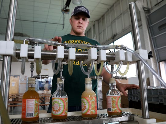 Mike Byrne, production assistant, fills Timbucha at Fairport Brewing's  new production space on University Ave.