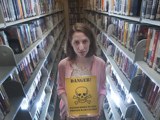 Collingwood library's Youth Services Assistant Sharon Clarke shows a banned book  sign at the Collingswood library in Collingswood. The Collingswood Public Library has banned book displays up in preparation for an upcoming book festival.