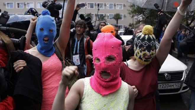 Russian punk group Pussy Riot members Nadezhda Tolokonnikova and Maria Alekhina make their way through a crowd after they were released from a police station in Adler, Russia, in 2014.