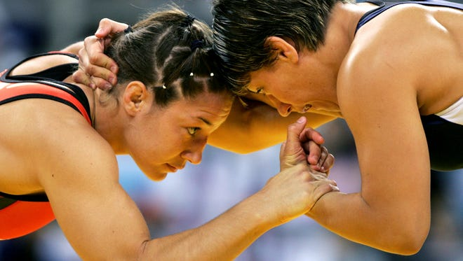 Former McDowell wrestling Sara McMann, left, now fights in the UFC.