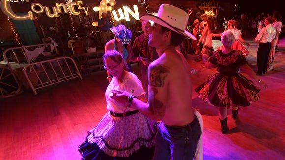 Vincent Robles of Reno dances with Lorie Abeles of Sun City during a square dance demonstration and lesson in the HonkeyTonk Dance Hall on Sunday, April 27, 2014 during the final day of the Stagecoach country music festival in Indio, Calif.
