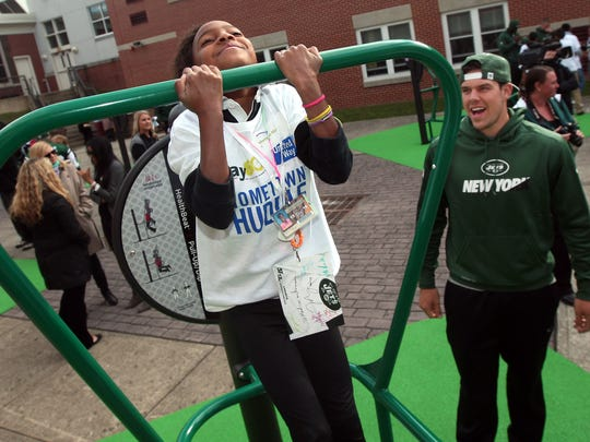 Ny Jets rookie quarterback Bryce Petty cheers on Madison Morris as she does chin-ups as members of the New York Jets unveil a PLAY 60 Fitness Zone playground with 35 students from Dover Middle School as part of the NFLÕs 17th annual Hometown Huddle, an NFL-wide day of service with United Ways across the nation. October 20, 2015, Dover, NJ