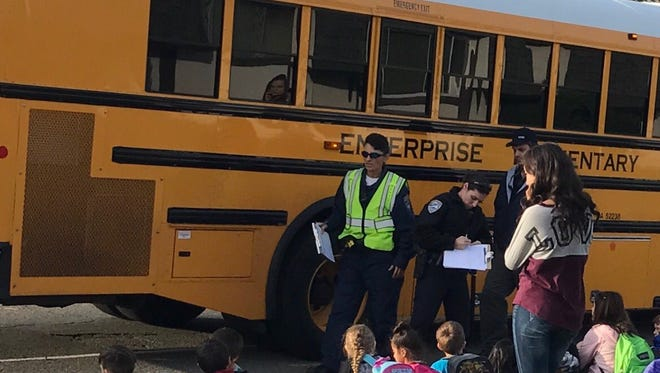 An officer talks with some of the students who were on the bus following the non-injury collision with a car.