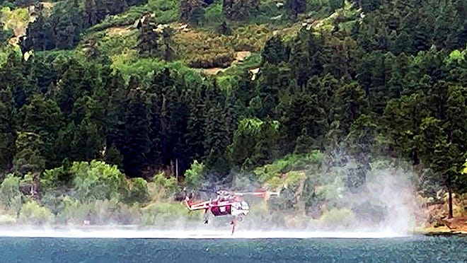 A helicopter extracts water from Lake Isabel to drop on the Willis Fire Tuesday. Helicopters were used again Wednesday to battle the blaze.