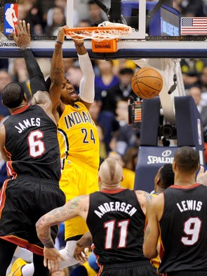 Indiana Pacers forward Paul George dunks the ball on Miami Heat forward LeBron James during the fourth quarter inside Bankers Life Fieldhouse, Wednesday, March 26, 2014, in Indianapolis.