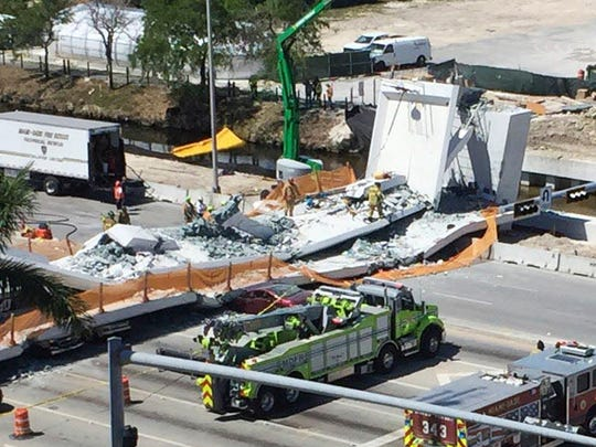 Emergency personnel respond to a collapsed pedestrian bridge at Florida International University on Thursday, March 15, 2018, in the Miami area. The brand-new pedestrian bridge collapsed onto a highway crushing several vehicles.