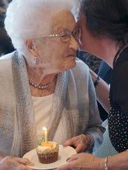Linda Wantin presents a birthday cupcake to Mary Slucter,