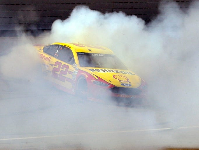 Joey Logano burns out on the track after winning the