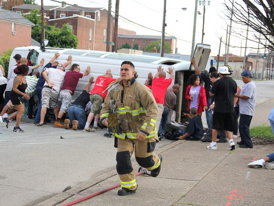 A firefighter runs as community members and emergency crews help out at a van crash.