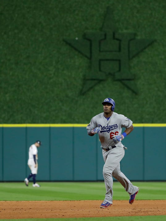 Los Angeles Dodgers' Yasiel Puig rounds the bases after a two-run home run against the Houston Astros during the ninth inning of Game 5 of baseball's World Series Sunday, Oct. 29, 2017, in Houston. (AP Photo/Matt Slocum)