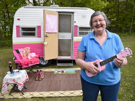 """Sue Notch holds a pink ukulele with other decorations in front of her camper Celia Rose Tuesday, May 17, at her home near Avon. Notch takes the 1965 camper on trips with Sisters on the Fly, an international """"glamping"""" organization."""