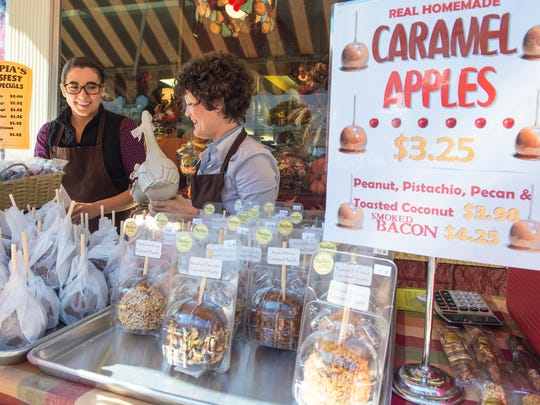 Rachel Myers, left, and Heather Yamamura sell caramel apples from Olympia Candy Kitchen during AppleFest on Saturday, Oct. 15, 2016 in downtown Chambersburg.
