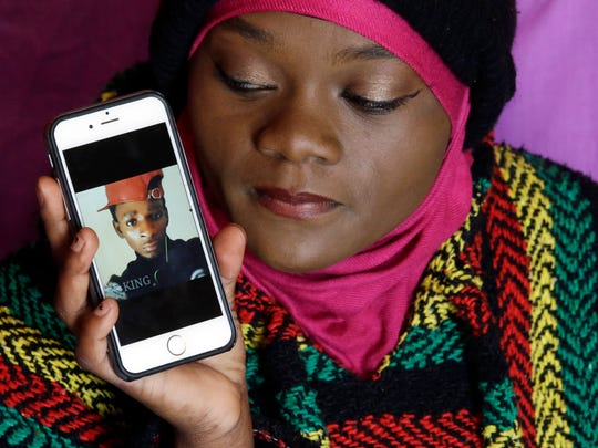 In this March 3, 2016 file photo, Muslima Weledi holds a photograph of her cousin Abdi Mohamed, a 17-year-old Somali refugee critically wounded in a high-profile police shooting in Utah, during a interview, in Salt Lake City. Salt Lake County District Attorney Sim Gill said officers acted appropriately when they fired at Mohamed because police believed he was about to seriously injure or kill a man with a metal broom handle.