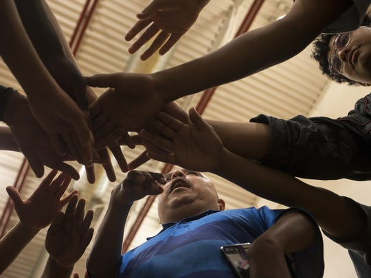 David Solano (center) and members of his basketball team huddle at the end of practice at Raul H. Castro Middle School.