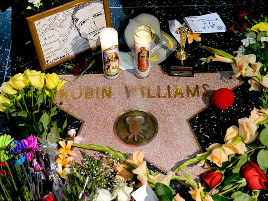 "Flowers are placed in memory of actor/comedian Robin Williams on his Walk of Fame star in the Hollywood district of Los Angeles, Monday, Aug. 11, 2014. Williams, a brilliant shapeshifter who could channel his frenetic energy into delightful comic characters like ""Mrs. Doubtfire"" or harness it into richly nuanced work like his Oscar-winning turn in ""Good Will Hunting,"" died Monday in an apparent suicide. He was 63. Williams was pronounced dead at his San Francisco Bay Area home Monday, according to the sheriff's office in Marin County, north of San Francisco."
