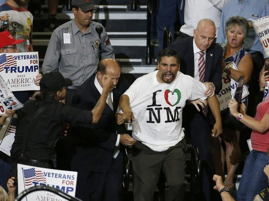 A protester is taunted by Trump supporters as he is removed during a speech by Republican presidential candidate Donald Trump at a campaign event in Albuquerque, N.M., Tuesday, May 24, 2016. (AP Photo/Brennan Linsley)