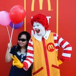 The McDonald's icon famous for his wild red hair, yellow jumpsuit and floppy shoes, has gotten a makeover from a theatrical stylist - really - who has updated just about everything but the shoes. In this file photo, Ronald McDonald poses with a customer during opening day of the first McDonald's in Vietnam.