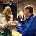 """USA Softball great Jennie Finch autographs a copy of her book, """"Throw Like A Girl,"""" at Friday's FCA Prayer Breakfast at Southern Miss."""