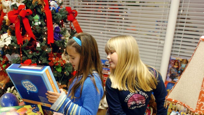 Holly Willingham, 8, right, looks over Miranda Farley's, 9, shoulder as they check out the mass of toys donated to the Toys for Tots campaign at Coldwell Banker Realty Group in Henderson Thursday evening, December 15, 2005. Willingham's grandfather Don Pinkstaff is a realtor at Coldwell. So far they have collected 788 toys, mainly from area schools. The high school students have given the most so far at over 200 toys. The toys will go to the Goodfellows Christmas Party, which will be held this Sunday at South Middle School. (Gleaner photo by Darrin Phegley ¥ 831-8375 or dphegley@thegleaner.com)