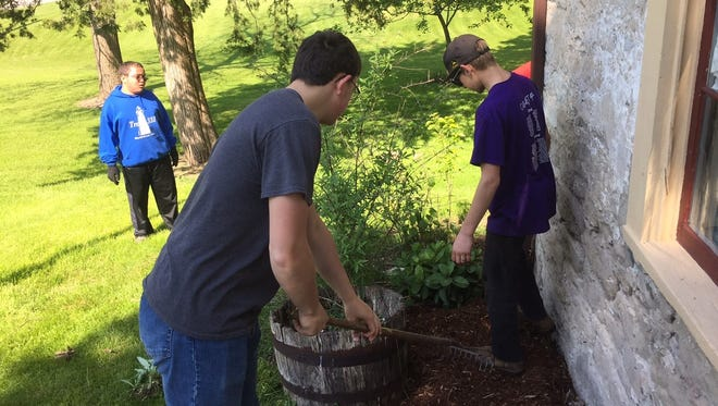 Members of Marblehead Boy Scout Troop 331 prepare a flower bed by the Keeper's House front door.