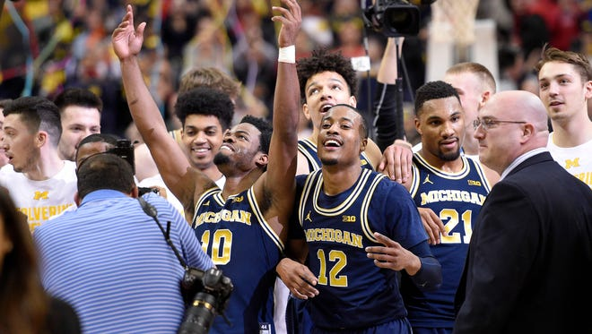 Michigan guard Derrick Walton Jr. (10), guard Muhammad-Ali Abdur-Rahkman (12) and guard Zak Irvin (21) celebrate after winning the Big Ten championship game over Wisconsin, 71-56, on Sunday, March 12, 2017 in Washington.