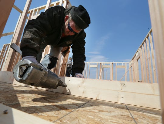 CM Construction owner Doug Morrill of West Des Moines nails framing for a wall as he builds a home in Waukee in 2014. New single-family home construction was down 10 percent in the Des Moines metro in 2018.