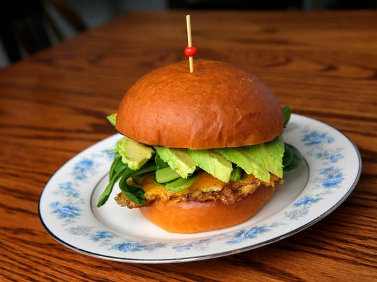 The Egg & Greens sandwich is made with a fried egg, cheddar, market greens, avocado and Dijon mustard on a brioche bun.