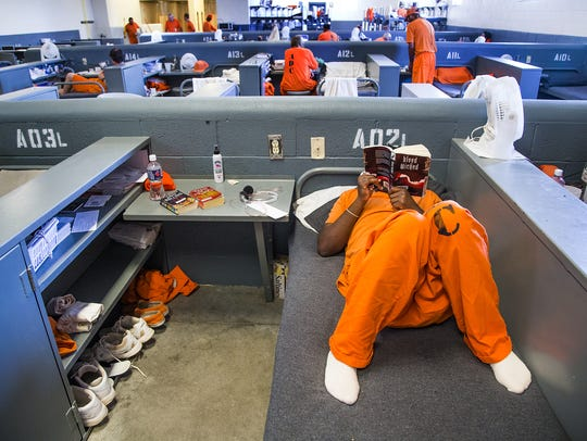 An inmate reads inside the prison.