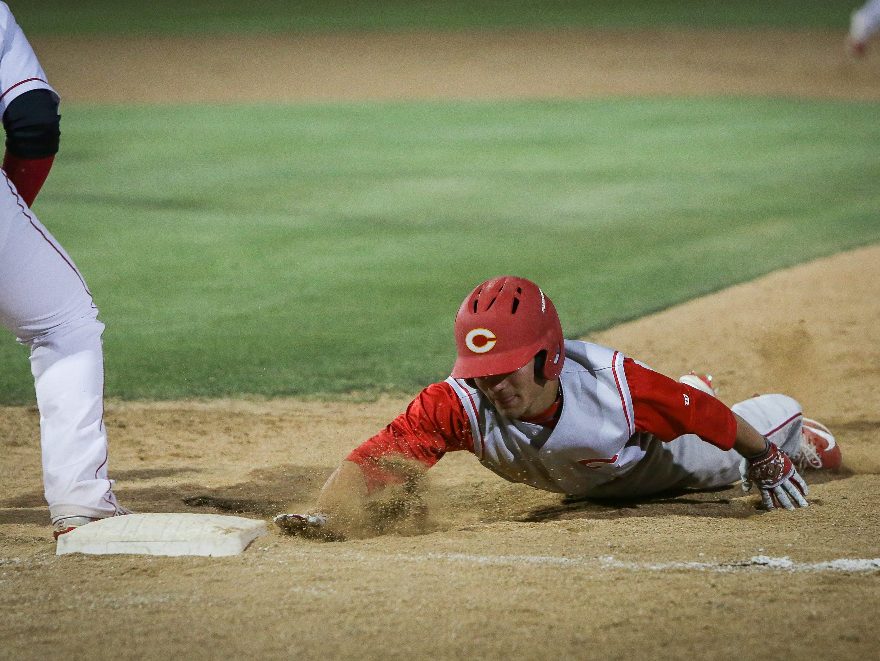 Corona's Chase Robison slides back to the first base.
