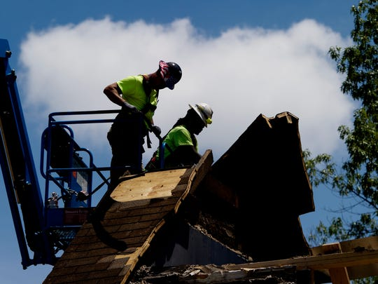 Workers remove roofing from the old Cowan Cottage outside the newly revamped Strong Hall on the University of Tennessee Knoxville campus in Knoxville, Tennessee on Friday, June 16, 2017.