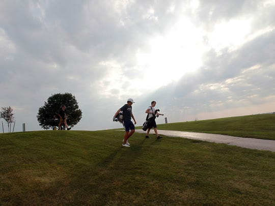 Cedar Rapids Prairie's Ian Johnston, center, heads down the fairway as he practices with teammates Dylan Kacena, left, and Stijn van den Boorn at Airport National Golf Course in Cedar Rapids on Wednesday, Sept. 20, 2017. Johnston started fundraising for the Area Substance Abuse Council after his brother, Seth Carnicle, died from a heroin overdose in October 2016.
