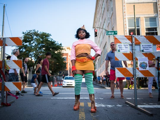 Francia Laguerre, of Asheville, poses for a portrait at the top of Lexington Avenue in an outfit made of repurposed clothing designed by McKinney Gough at the Living Asheville Arts Festival or LAAF, Saturday, September 3, 2017.