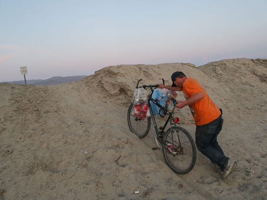 Robert Pruitte struggles to push his bike carrying his groceries up a dirt embankment near the area where he stays in a structure he built in the open desert in Coachella.