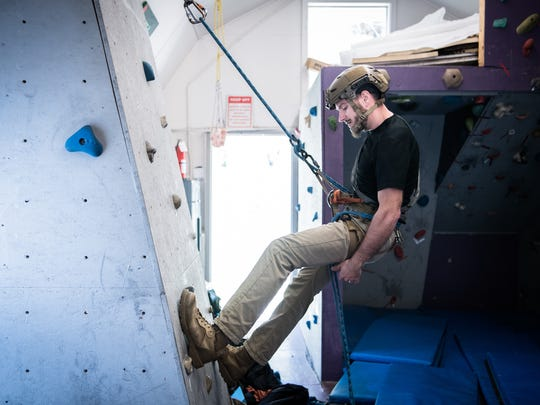 Matt Draughon, a student in Southwestern Community College's Outdoor Leadership program practices reppelling  in the school's climbing gym.