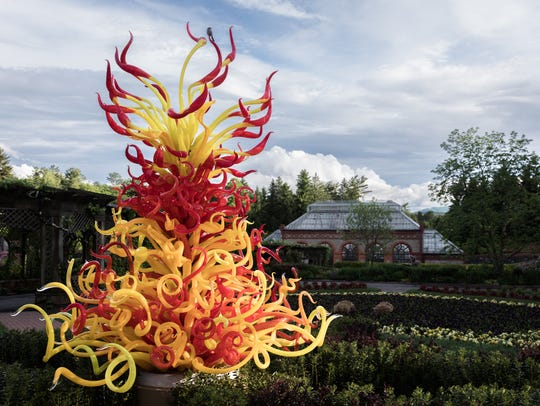 A tower of blown glass titled Paintbrush Tower within the Walled Garden at the Biltmore estate which is part of the Chihuly at Biltmore exhibition of a collection of Dale Chihuly's work.