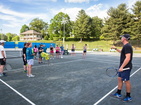 Brett Caldwell, one of the instructors of the Try Tennis program offered through the Asheville Tennis Association talks to students during their last class at the Aston Park tennis courts, Monday, May 21, 2018.