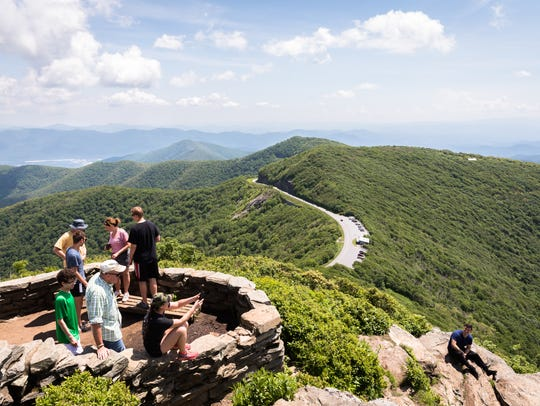 Hikers take in the view at the summit of the Craggy