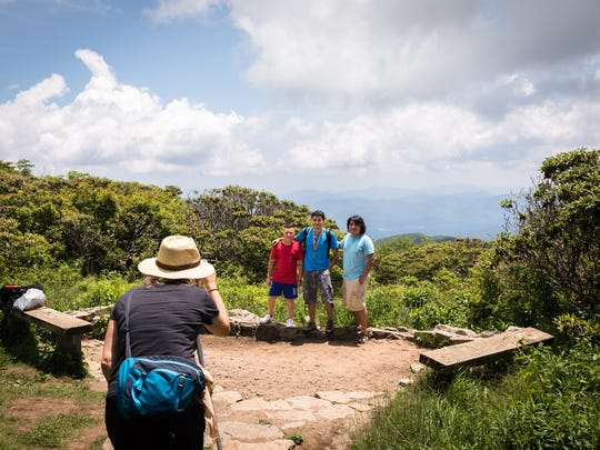 Erick Payes, Nathan Munos, and Christian Arevalo, of Charlotte, pose for a photograph at the summit of the Craggy Gardens trail Friday, June 15, 2018.