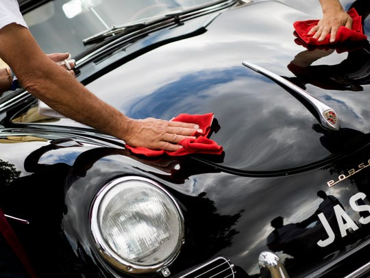 A classic Porsche car is polished during the Goodwood