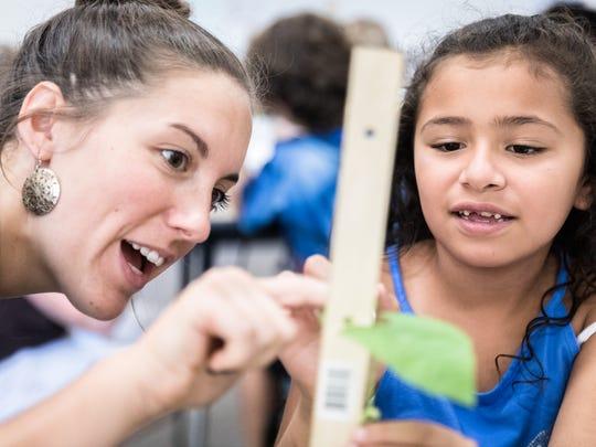Nikki Bush, a kindergarten teacher at Isaac Dickson elementary school, helps Amaite Varela, 7 with measuring her lima bean plant during Asheville City Schools' Summer Reading Camp at Hall Fletcher Elementary School, Wednesday, July 25, 2018.