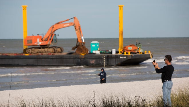 Two construction barges are stuck in the sand along the beach at Lowdermilk Park in Naples early Tuesday, Jan. 30, 2018.