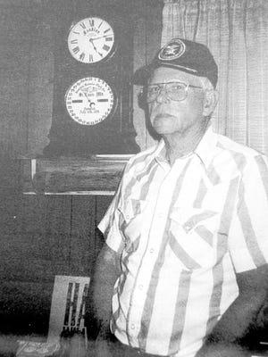 Bob Reed with his grandfather's clock, a scrolled-top Seth Thomas Fashion Calendar Clock.