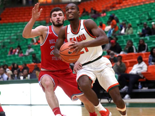 FAMU's Justin Ravenel drives past Delaware State's Artem Tavakalyan at the Al Lawson Center on Monday, Jan. 15, 2018.
