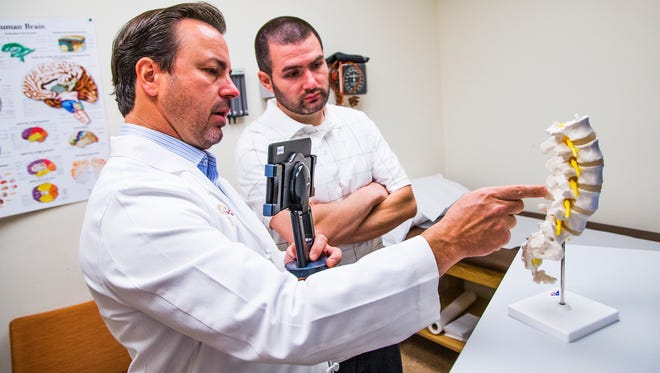 Dr. Randall Porter, left, a neurosurgeon at Barrow Neurological Institute, holds a tablet to video a consult with patient Julio Carbajal, on March 9, 2015. The system, called The Medical Memory, allows patients to replay their consults with their doctors.