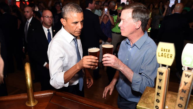 President Obama and Colorado Gov. John Hickenlooper toast their beers at a pub in Denver on July 8, 2014.
