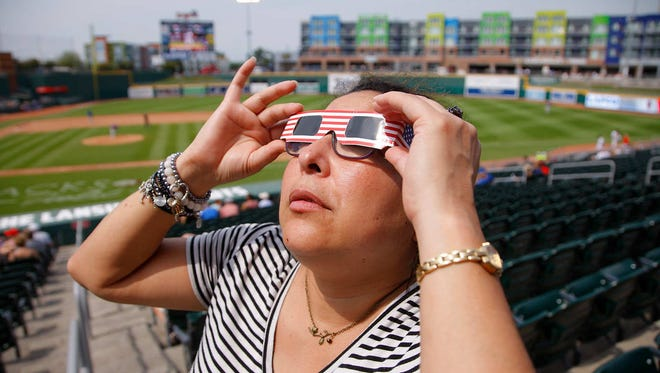 Natalie Harper watches the eclipse during a Lansing Lugnuts game, Monday, Aug. 21, 2017, at Cooley Law School Stadium. The Lugnuts celebrated the eclipse by giving out free viewing glasses and scheduling a delay in the game specifically for eclipse viewing.