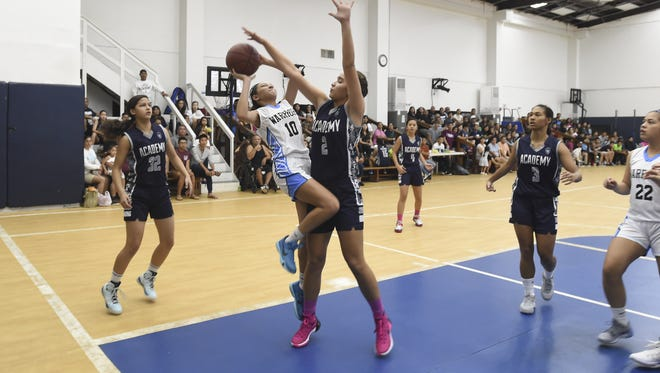 Academy of Our Lady of Guam cougar Mia San Nicolas (2) makes the block on St. Paul's Haley Senne (10) during their Independent Interscholastic Athletic Association of Guam Girls Basketball League game at St. Paul Christian School gym in Dededo on Nov. 14.