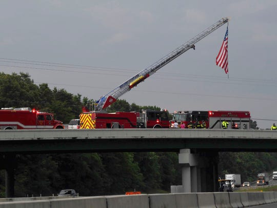 Fire department personnel stand on an I-40 overpass