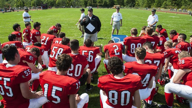 CVU head coach Mike Williams talks to the team during halftime of a high school football game between the Rutland Raiders and the Champlain Valley Union Redhawks on Saturday afternoon.