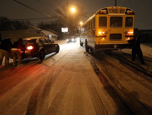 People work to push a stuck Atlanta school bus and a car on an icy stretch of University Avenue in southwest Atlanta on Jan. 28.